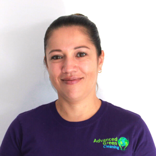 a lady with a neatly kept hair smiling at the camera wearing purple shirt with the company logo of advanced green cleaning Albuquerque