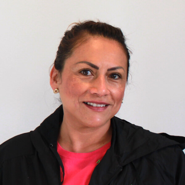 a lady smiling at the camera with a nicely drawn brows, she's wearing a pink shirt with the company logo and a black jacket