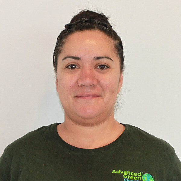 a woman smiling at the camera with a neatly kept hair, she's also wearing a green shirt with a company logo of advanced green cleaning