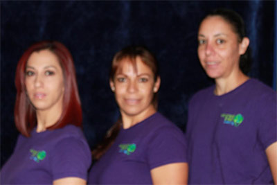 three woman, a red hair, a blond and a black haired. They are wearing purple shirts with the company logo advanced green cleaning Albuquerque