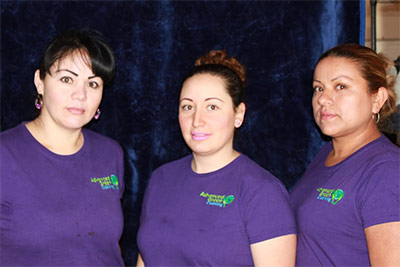three ladies with neatly kept hair smiling at the camera, they are wearing violet company shirt with the company logo of advanced green cleaning Albuquerque