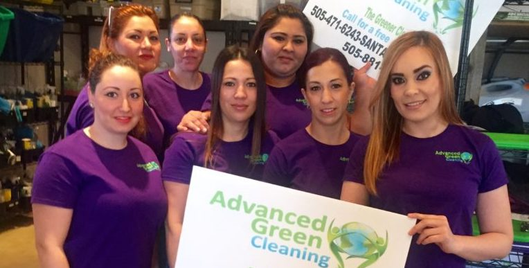 seven woman smiling at the camera wearing a purple shirt with the advanced green cleaning logo, they are also holding advanced green cleaning logo in a big banner