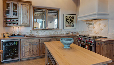 a kitchen interior that has a classical theme designs, at the middle is a wooden table and a clay bowl, it also has some drawers below and over the stove and sink, and it also has glass windows and a frame