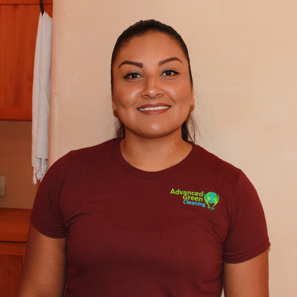 a woman with a neatly kept hair smiling at the camera wearing a maroon shirt with the advanced green cleaning Albuquerque logo