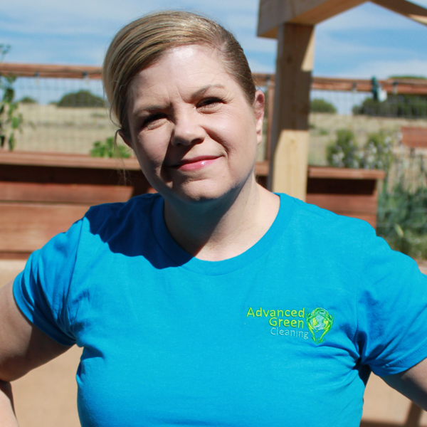 a blonde woman smiling at the camera, she's wearing a blue shirt with the advanced green cleaning Albuquerque logo