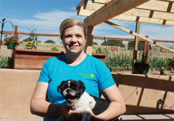 a smiling blonde woman wearing a blue shirt with the company logo santa fe cleaning company carrying a shih tzu dog she is in some sort of balcony