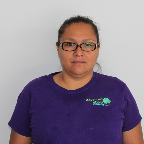 a woman wearing an eyeglasses and a purple shirt with the logo of advanced green cleaning albuquerque