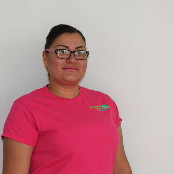 a woman smiling at the camera wearing a pink eyeglasses and a pink shirt with the logo of advanced green cleaning Albuquerque