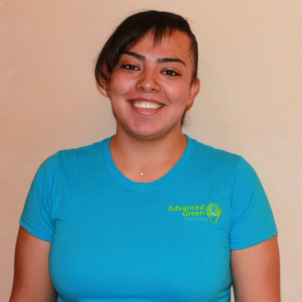 a woman with an undercut with side bangs smiling at the camera, she's wearing a sky blue shirt with the advanced green cleaning Albuquerque logo