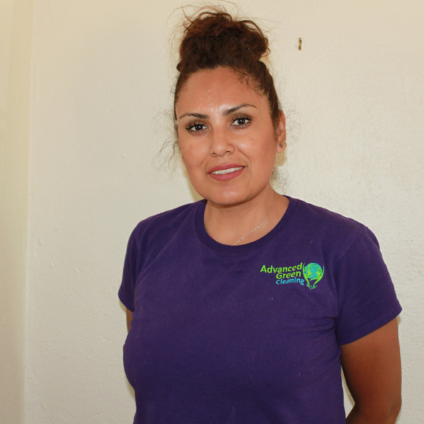 a woman with some sort of beehive hairstyle wearing a purple shirt with the advanced green cleaning Albuquerque logo