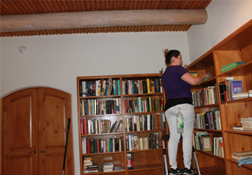 a woman wearing a violet shirt, she is using a ladder because she's arranging books in a brown bookshelf beside the bookshelf is a wooden door