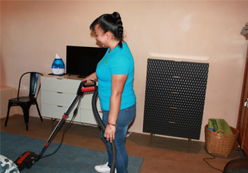 a women wearing blue shirt cleaning a room with a red vacuum cleaner the room has dark blue mat, a tv and a black chair she's from santa fe cleaning company