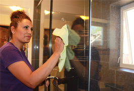 a lady with brown and neatly kept hair cleaning a glass window with a santa fe cleaning company cloth