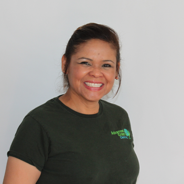 a cheerful woman smiling at the camera she's wearing a red earrings and a green shirt with the logo of advanced green cleaning Albuquerque