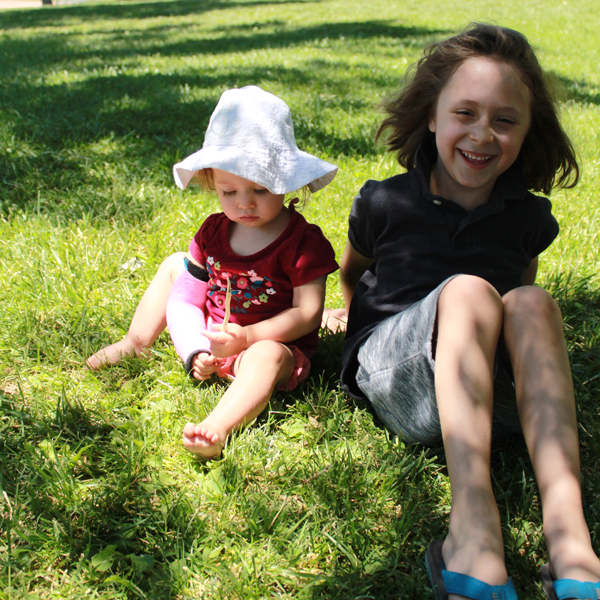 a toddler wearing a white hat and a kid sitting in a green grass