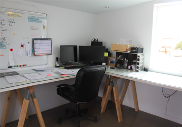 an office desk with an office chair, the computer has two screen connected to it, in the white wall are a lot of papers which is for reminders