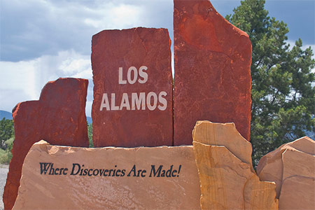 A stone trademark colored red and brown, the middle stone has Los Alamos in it and the brown ones has Where discoveries are Made painted on it