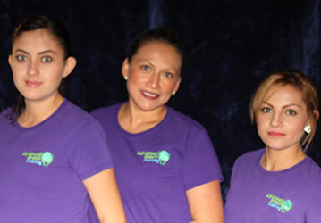 three women with neatly kept hair smiling at the camera wearing violet shirts with the logo of advanced green cleaning