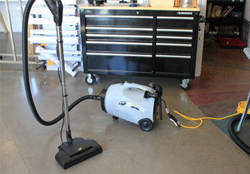 a white and black power cleaning vacuum cleaner and a black table with wheels